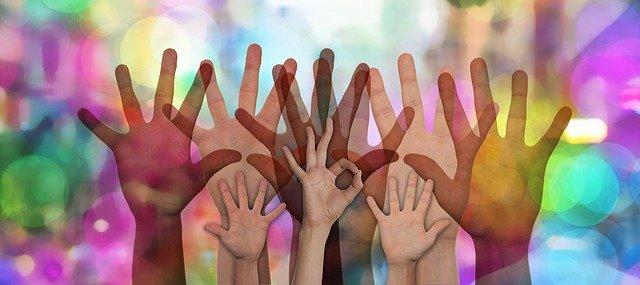 groupe de mains levées sur fond coloré en singe de solidarité